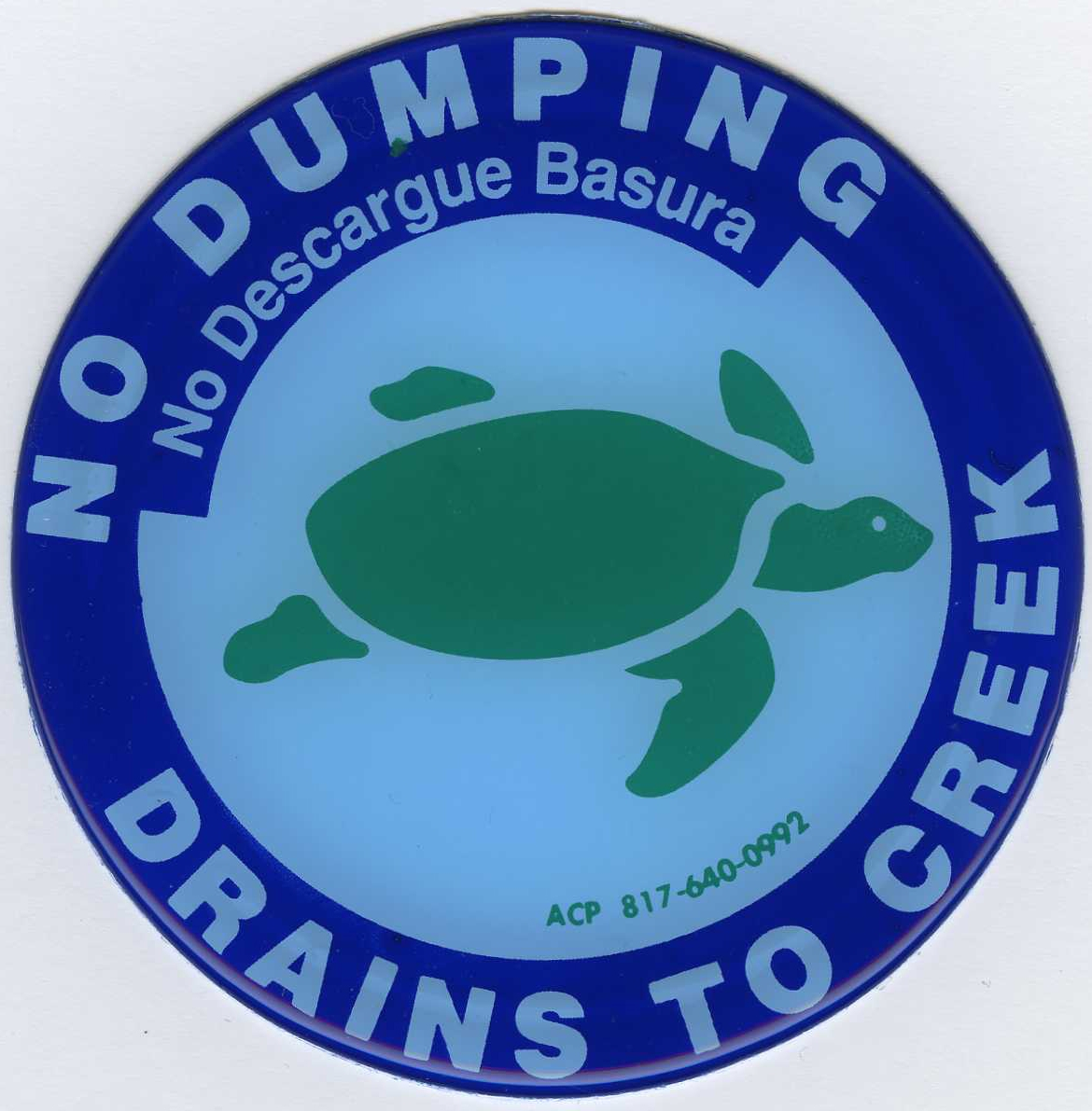 """No Dumping Drains to the Creek"" seal that is placed on sewers."