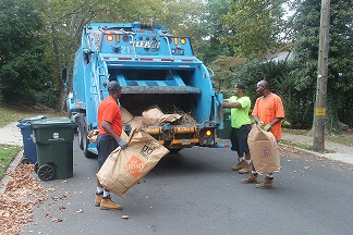 Public Works workers collecting yard debris bags in a neighborhood.