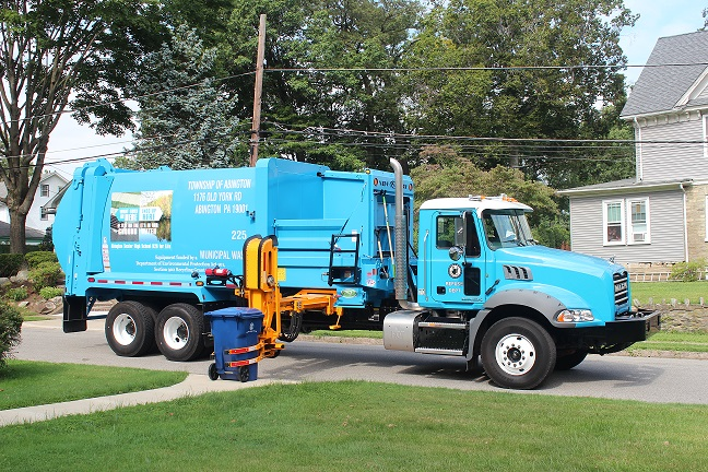 Abington Township recycling truck collecting recyclables along the street.