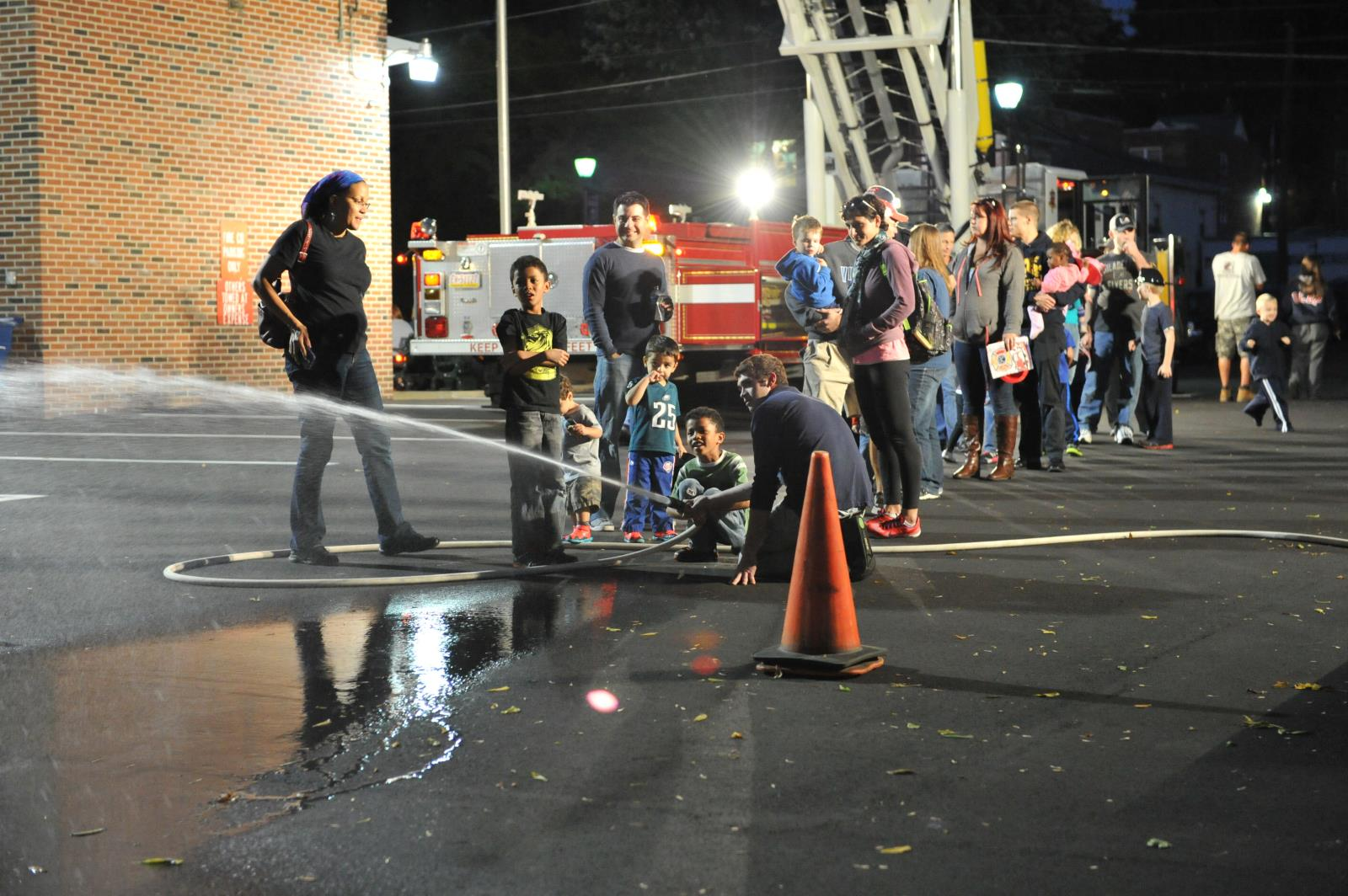 Kid spraying fire hose at fire station open house