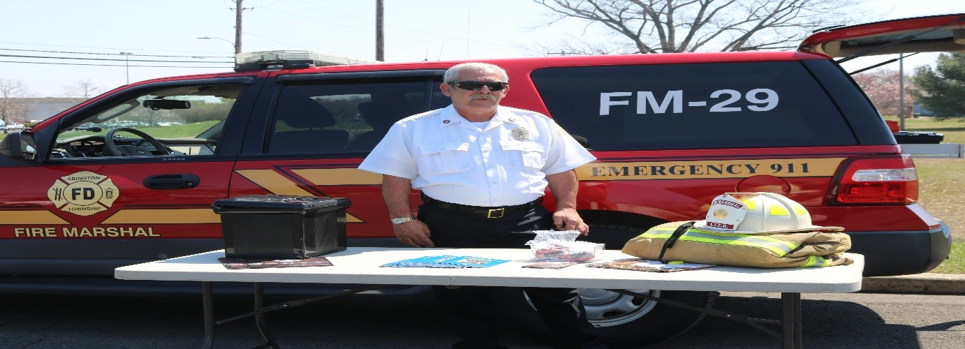 Fire Marshal standing at a table at a community event.