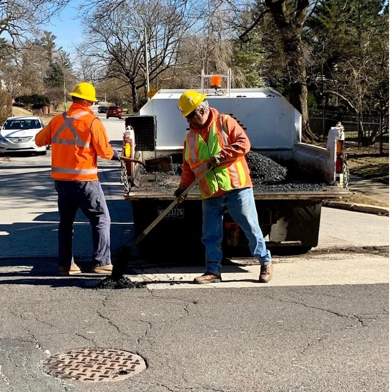 Public Works employees filling in road potholes