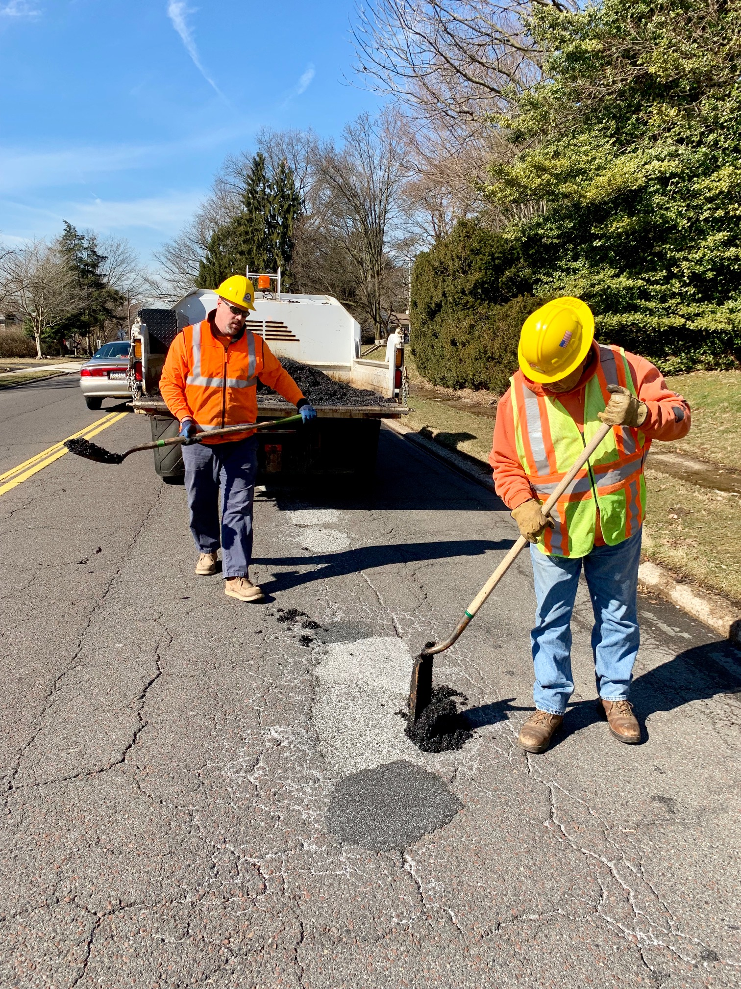 Public Works workers filling in pothole on road.