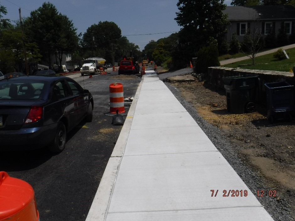 New concrete sidewalk curb on the south side of Tyson Ave.